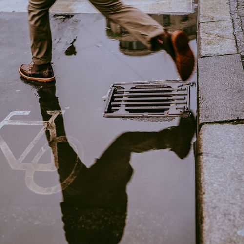 Low section of man jumping over puddle