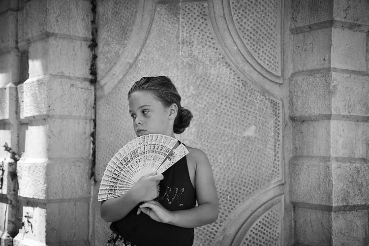 Little girl posing with folding fan against building