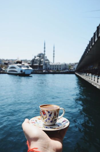 Cropped Image Of Person Holding Tea Cup By Sea