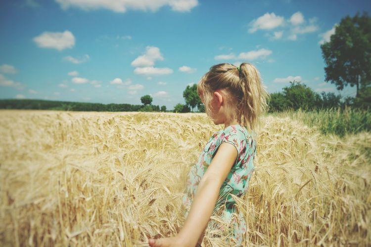 Side View Of Girl Standing In Wheat Field Against Sky