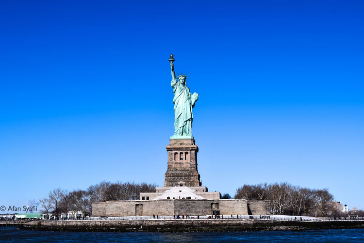 America Architecture Archival City Clear Sky Cultures Day Female Likeness Liberty Liberty Island Liberty Statue Monument New York New York City No People Outdoors Representing Sculpture Sky Statue Travel Destinations Tree USA Water Winter