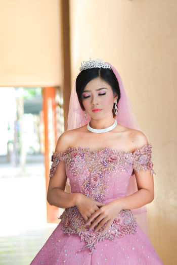 Beautiful young bride wearing wedding dress while standing at home