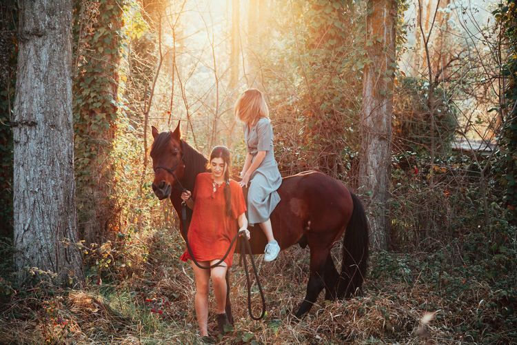 Women with horse in forest