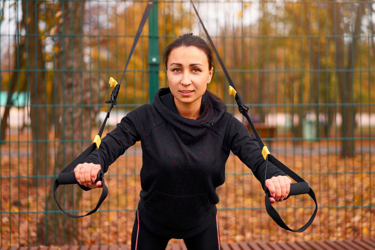 Portrait of smiling woman exercising with equipment against fence