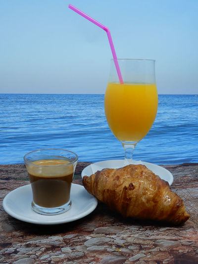 Breakfast on table by sea against sky
