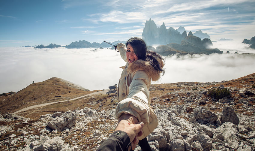 Beautiful young woman is pointing at the Cadini Group in the Dolomites Mountain One Person Leisure Activity Scenics - Nature Beauty In Nature Cloud - Sky Lifestyles Tranquil Scene Nature Young Adult Outdoors Day Rock Showing Woman Dolomites, Italy Cadini Di Misurina Fog Mist Beautiful Travel Vacations Travel Destinations Landscape Mountain Scape