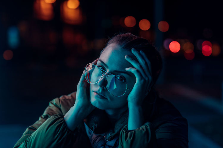 Portrait Of Young Woman Wearing Eyeglasses Against Illuminated Lights At Night