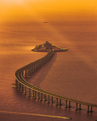 High angle view of road by sea against sky during sunset