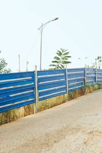 Fence on road against clear sky