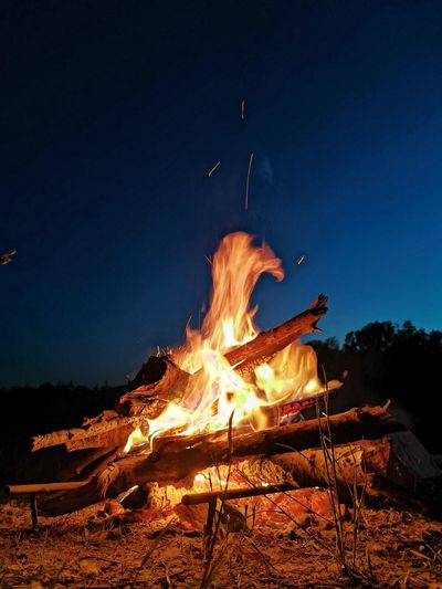 Bonfire on wooden structure against sky at night