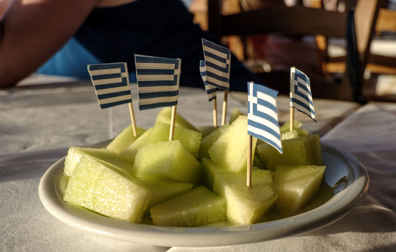 Small greek flags stuck in fruit slices on plate