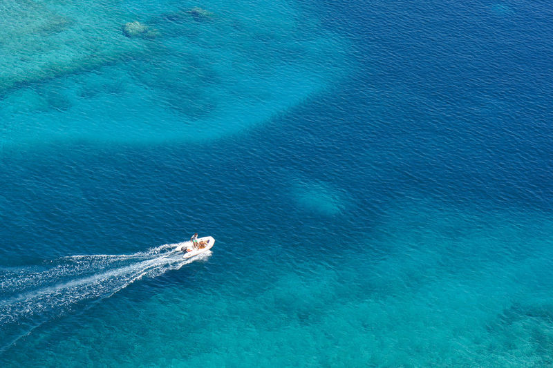 High angle view of turquoise sea with speed boat