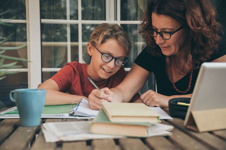 Boy with mother studying at home