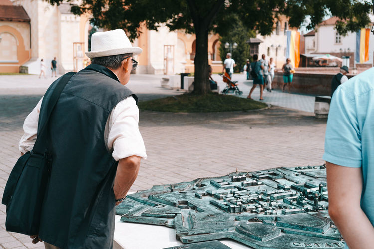 Curious tourist City Street Real People Day Nature Outdoors Travel Travel Destinations Traveling Tourism Tourist Tourist Attraction  Histroy  Historic Map 3D Representation Medieval MedievalTown Cobblestone Tree Park Old City The Past Nature