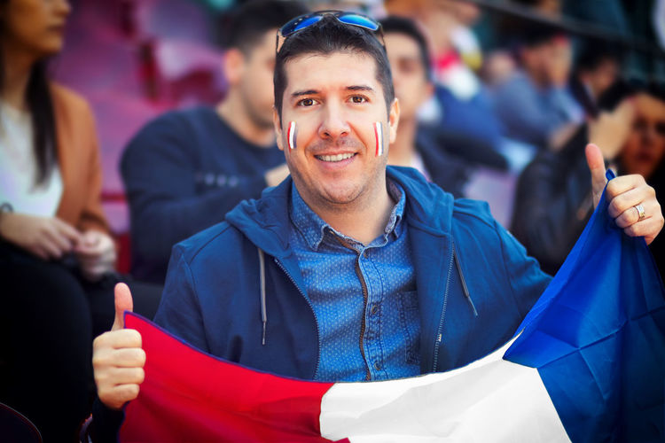 Happy supporter holding french national flag in hands at international football match