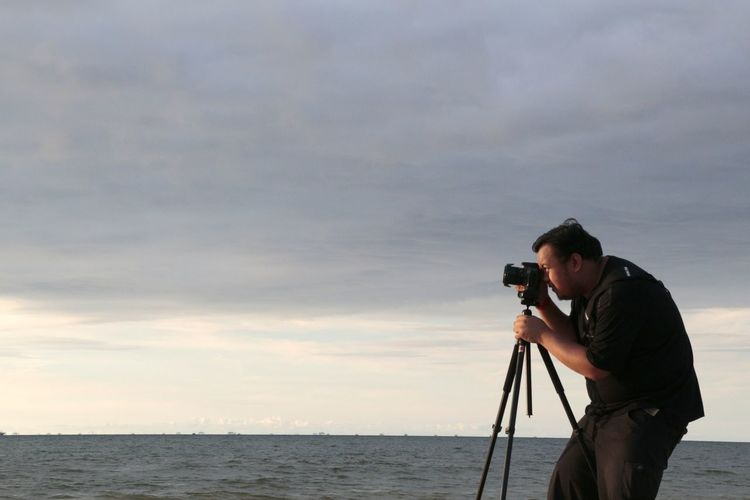 Man photographing at beach against sky
