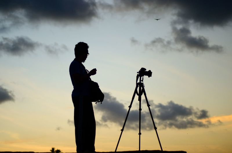 Scenic view of photographer silhoutte on the sunset background. Photography Themes Full Length Sunset Camera - Photographic Equipment Standing Silhouette Men Photographing Side View Tripod Cloudscape Dramatic Sky Moody Sky Sky Only Photographer