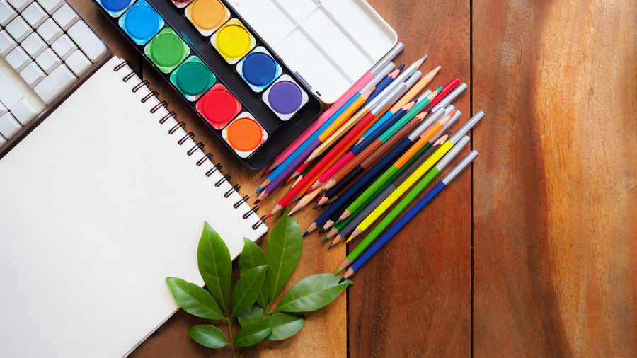 Place of work, blank white color paper page and colorful pencil on vintage wooden desk, creative graphic designer artist concepts for business and education background Still Life Art Drawing ArtWork Creative Table Choice Design Artist Art And Craft Supplies Book Sketchbook Craft Pencil Graphic Design Creativity Indoors  Watercolor Workplace Colored Pencil Education Close-up Designer  Variation No People Green Color Watercolor Painting High Angle View Directly Above Large Group Of Objects Multi Colored Wood - Material Book Pages Drawing - Art Product Writing Instrument Art And Craft Equipment Indoors  Pen