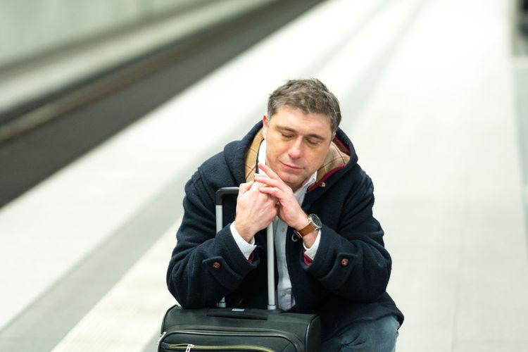 Man with luggage sleeping at railroad station platform