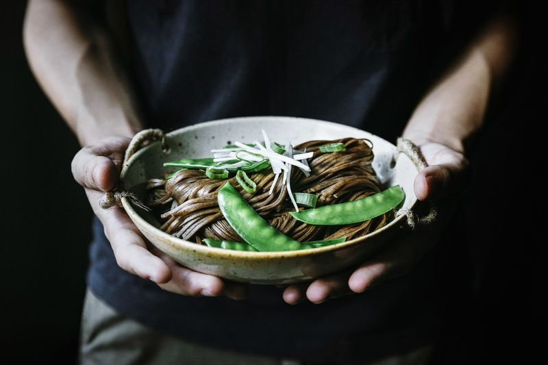 Midsection of man holding food bowl against black background