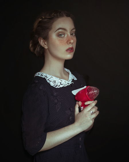 Portrait of beautiful young woman with toy standing black background