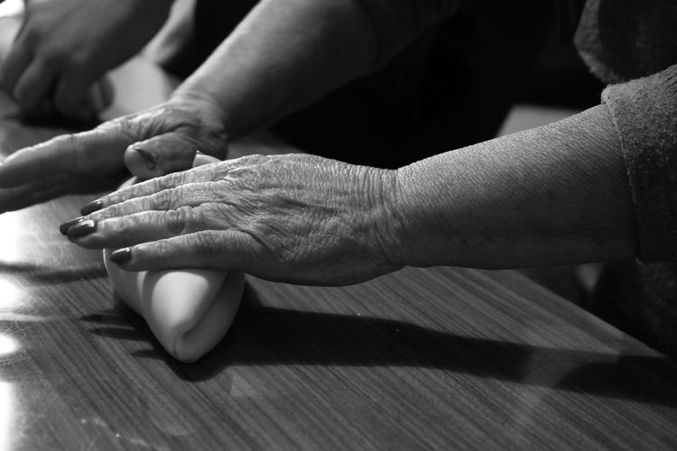 High angle view of hands kneading dough