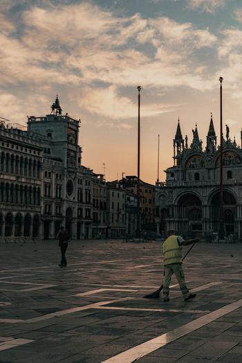 Rear view of people walking on street by buildings against sky