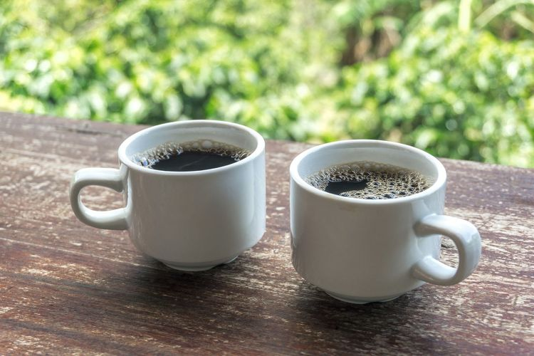 two cups of coffee on angled wood table with bokeh background Coffee Bokeh Green Coffee Background Costa Rica Tea - Hot Drink Frothy Drink Black Coffee Hot Drink Non-alcoholic Beverage