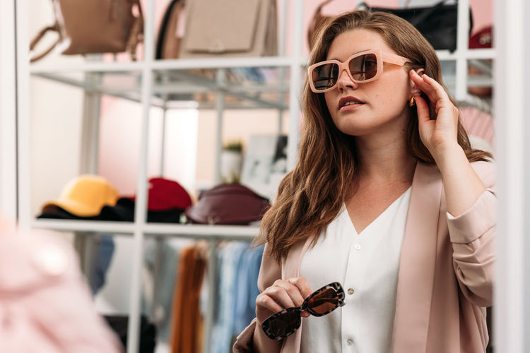 Midsection of woman holding sunglasses standing outdoors