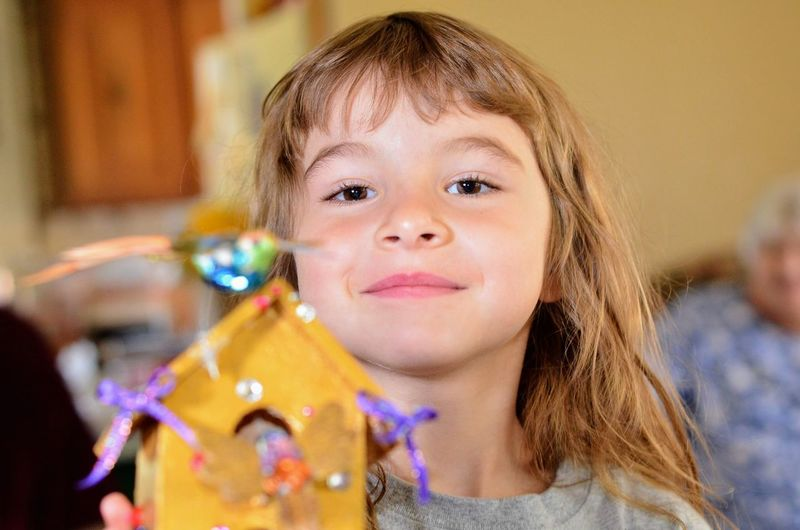 Close-Up Portrait Of Cute Smiling Girl Holding Toy Home
