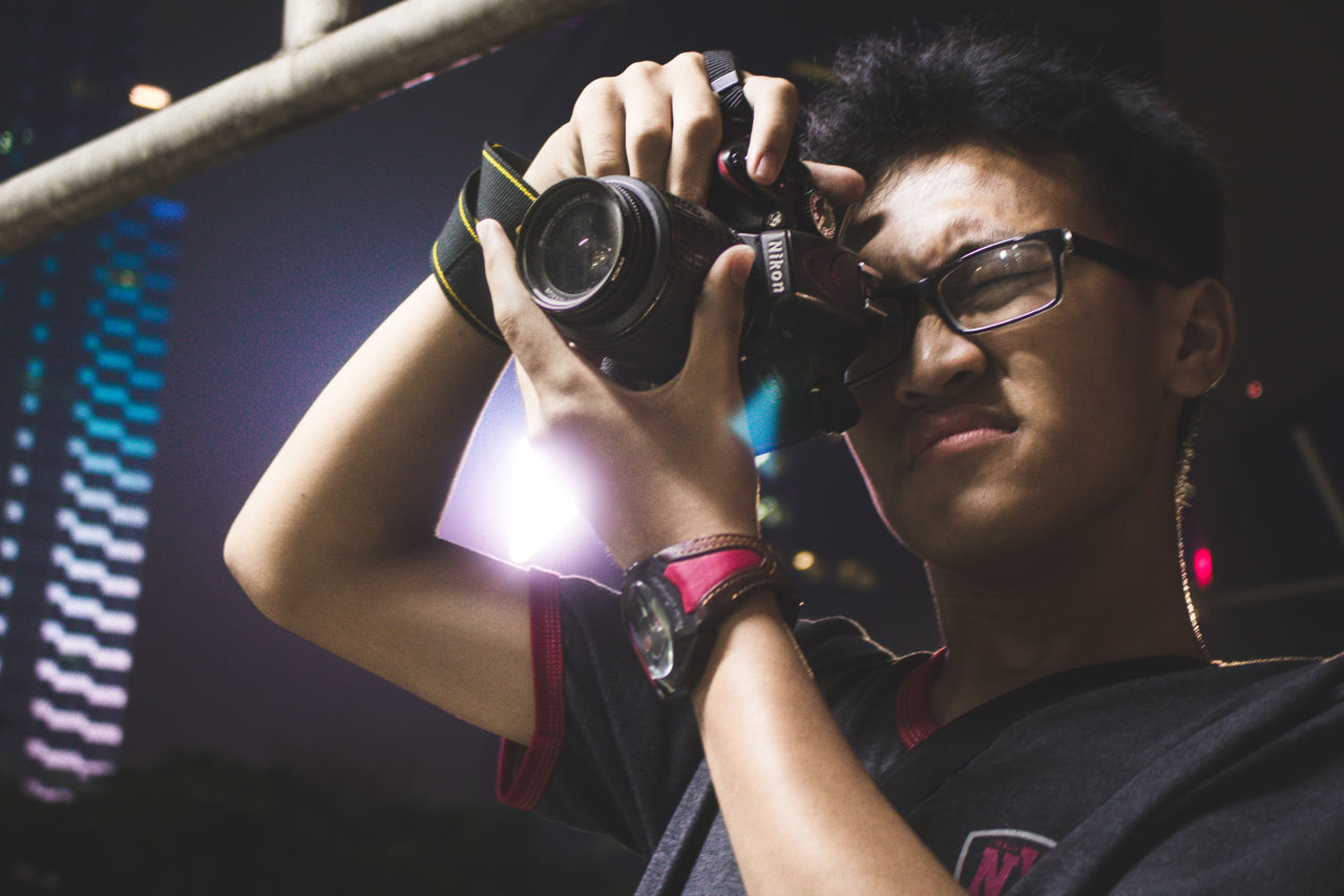 PORTRAIT OF YOUNG MAN WITH CAMERA