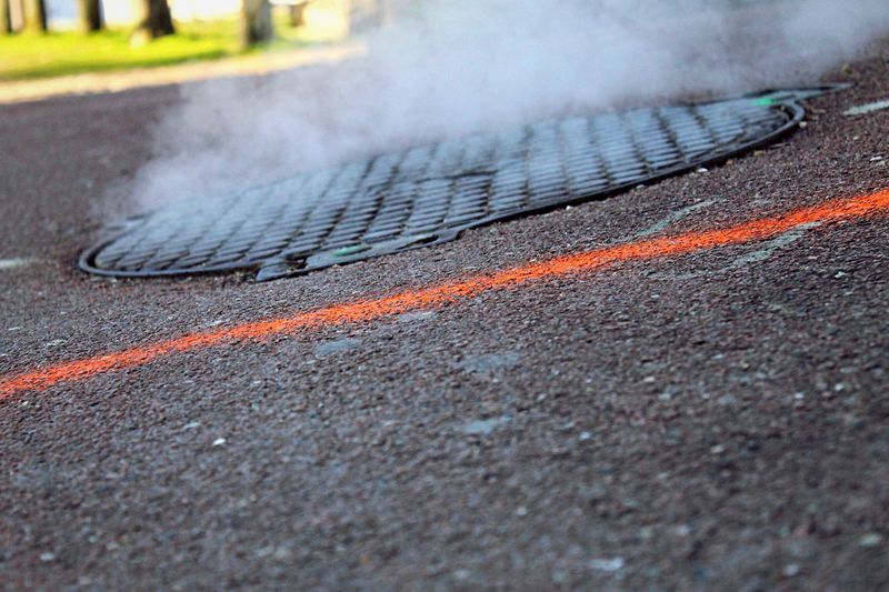 Close-Up Of Steam From Manhole Lid On Road