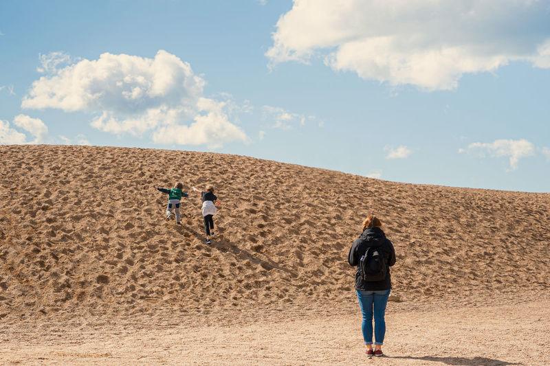 Rear view of people walking on sand dune in desert