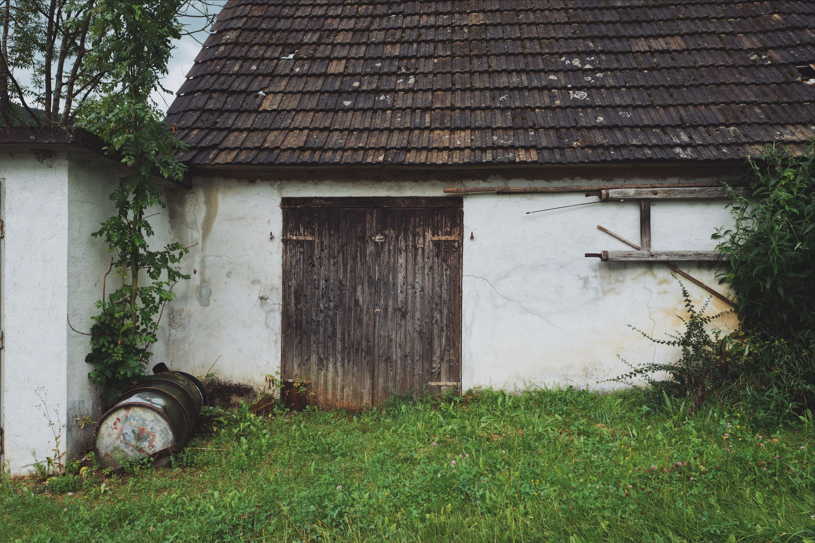 architecture, built structure, building exterior, plant, grass, building, day, house, no people, nature, abandoned, old, green color, roof, outdoors, rural scene, damaged, window, landscape, residential district, wheel, roof tile, garage