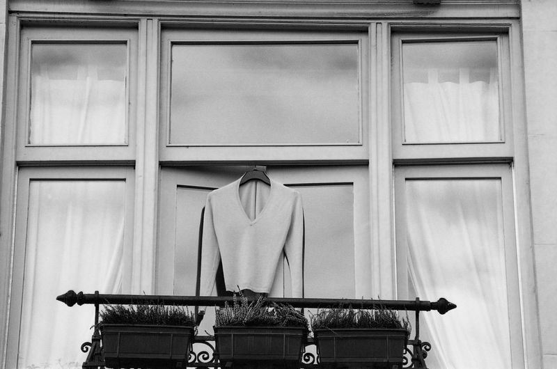 Pullover hanging outside a window, monochrome, absence