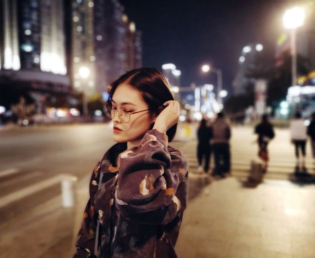 Woman standing on city street at night