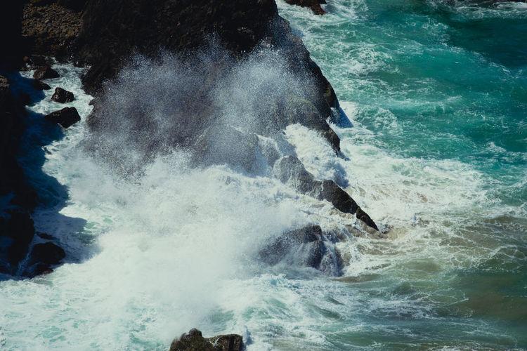 Waves splashing in sea against cliff