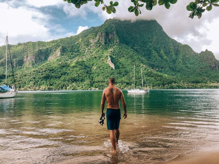 Rear view of shirtless man walking in sea