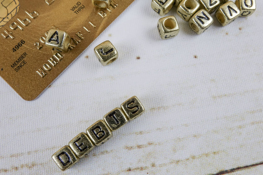 DEBT CONCEPT WITH GOLD DICE ON A WOODEN TABLE Business Capital Letter Close-up Communication Credit Card Debt Crisis Gold Colored High Angle View Indoors  Jewelry Letter Metal No People Number Paper Ring Still Life Studio Shot Table Text Wealth Western Script