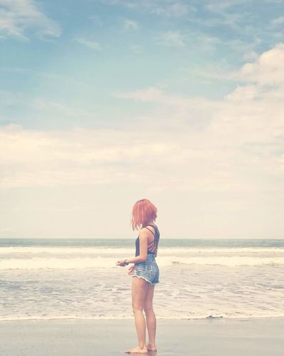 Young Woman Standing On Shore Against Cloudy Sky