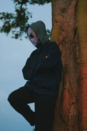 Side view of man with obscured face standing against tree trunk