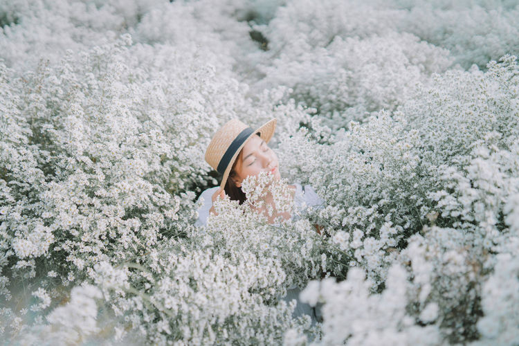 Young woman with closed eyes sitting amidst flowering plants