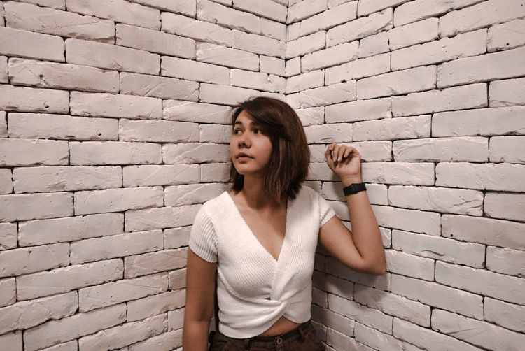 Young woman standing against wall