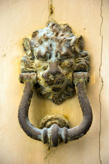 Old rusty iron lion head door knocker on a white door. Mdina, Malta Bronze Entrance Iron Lion Lion Head Malta Ornament Valletta,Malta Brass Close-up Detail Door Doorway HEAD Knob Knocker Knocking Lock Mettalic No People Object Old Rusty Vintage Wooden Door