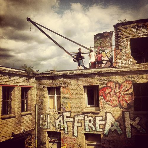 Architecture Berlin Building Exterior Built Structure City Cloud - Sky Crane Day Eisfabrik Graffiti Graffiti Art Low Angle View No People Oldbuilding Outdoors Rooftop Ruined Building Sky Text Travel Destinations