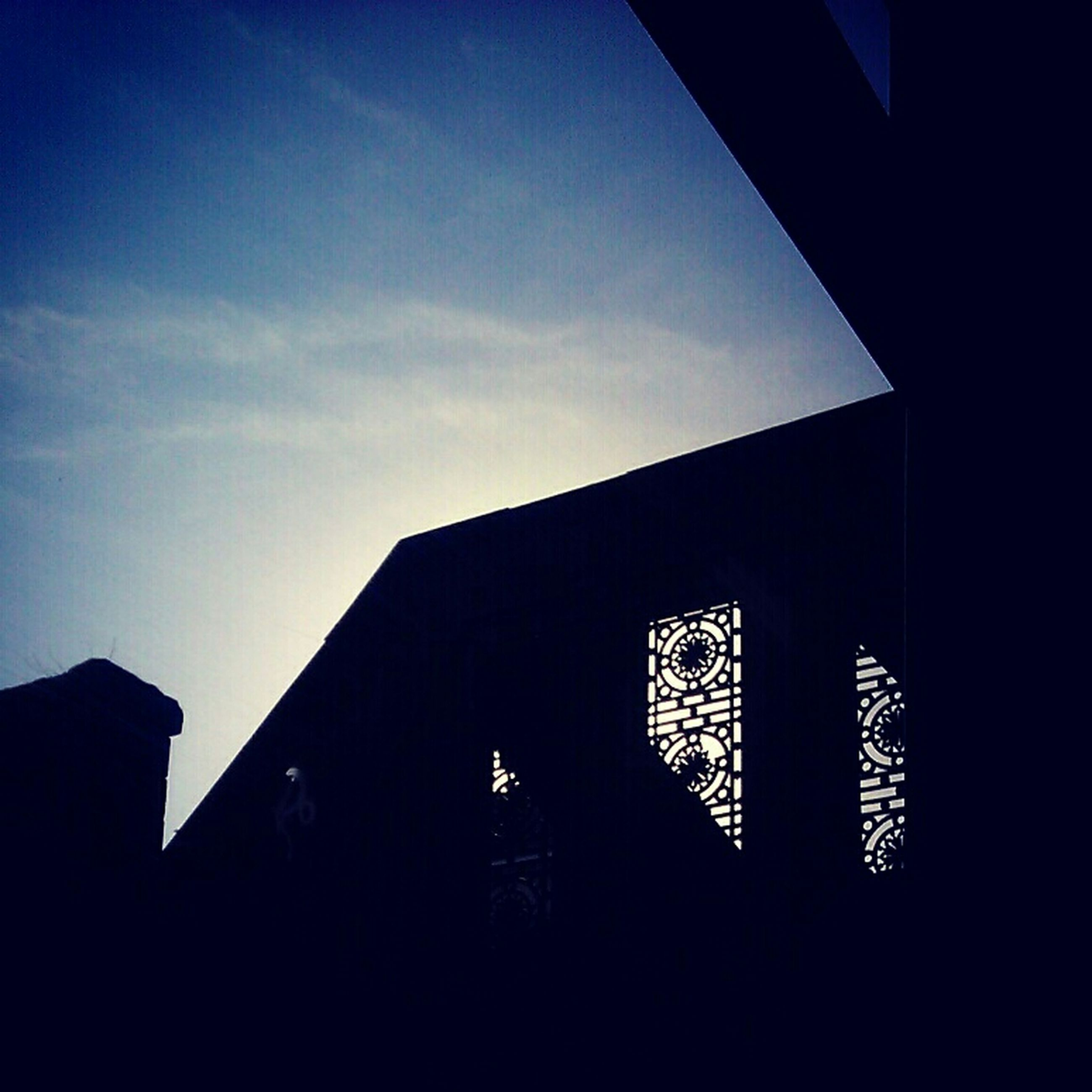 architecture, built structure, silhouette, building exterior, low angle view, sky, sunset, dark, window, sunlight, dusk, outdoors, no people, blue, building, house, cloud, outline, copy space, day