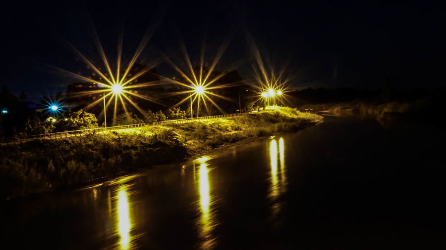 Illuminated street lights by river against sky at night