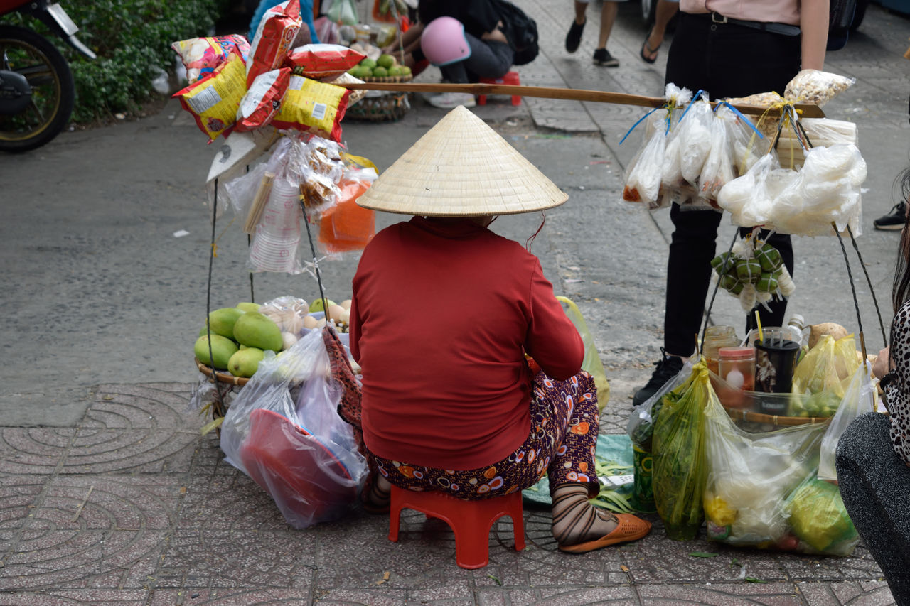 selling, real people, asian style conical hat, women, rear view, occupation, retail, one person, day, outdoors, full length, food, sitting, men, working, adult, people