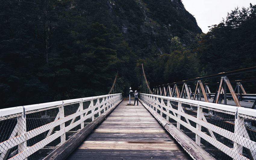 Mid Distance Of Person Standing On Footbridge Against Mountain