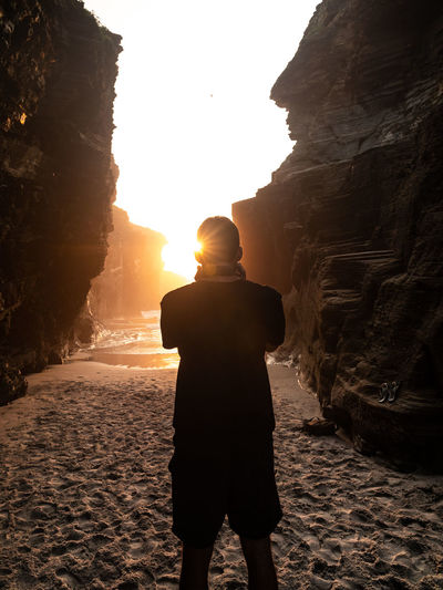 Rear view of man standing by rock formation at beach during sunset